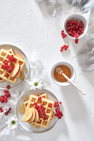 Flat lay of traditional belgian waffles with fresh fruit, nectarine, currant and honey on white background. Breakfast. Top view with copy space. Stock Photo