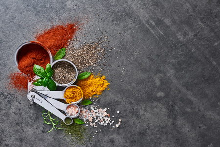 Flat lay of various spices in measuring cups with fresh basil and mint on stone table. Top view with copy space.