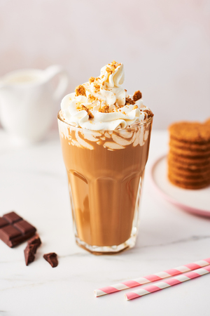 Chocolate ice coffee with whipped cream and cookies in a tall glass with pink straws on white marble table over rose background. High resolution image with copy space and selective focus.