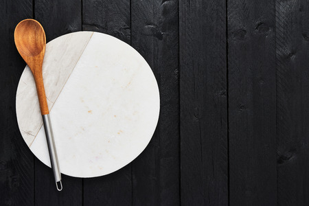 Top view of white marble serving plate and wooden spoon on black wooden table with copy space. Food background concept.