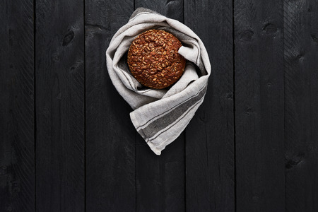 Whole wheat bread on black wooden table. Rustic food background concept. Top view.