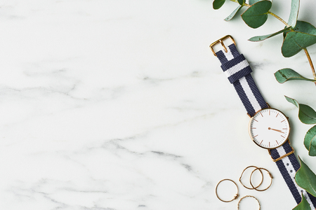 Womens watch with navy blue and white nylon strap, golden rings and eucalyptus on white marble background. Top view with copy space for text. Stok Fotoğraf