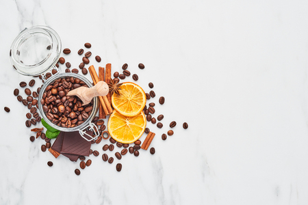 Coffee in a glass jar with beans, chocolate, dried oranges, anis and cinnamon sticks on white marble background. Concept of coffee with different spices. Top view with copy space for text.