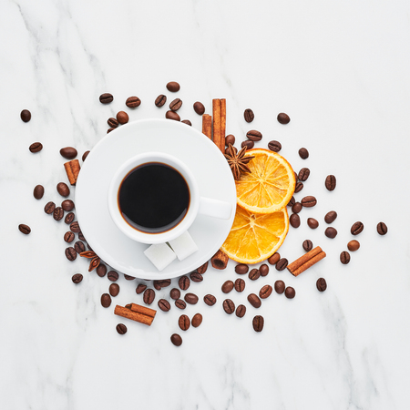 Cup of coffee with beans, chocolate, dried oranges, anis and cinnamon sticks on white marble background. Concept of coffee with different spices. Top view, square crop. 写真素材