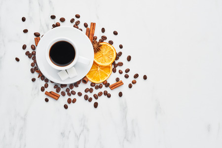 Cup of coffee with beans, chocolate, dried oranges, anis and cinnamon sticks on white marble background. Concept of coffee with different spices. Top view with copy space for text.