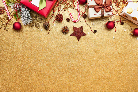 Beautiful christmas red deco baubles with gifts on golden glitter background. Flat lay design. Copy Space. Horizontal. Stock Photo