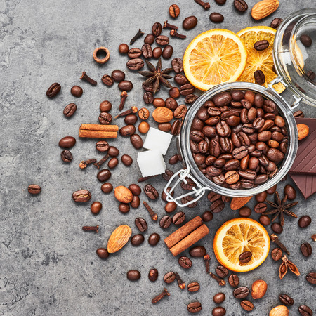 Coffee in a glass jar with beans, chocolate, dried oranges, anis and cinnamon sticks on grey concrete background. Concept of coffee with different spices. Top view, square crop.