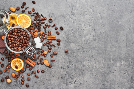 Coffee in a glass jar with beans, chocolate, dried oranges, anis and cinnamon sticks on grey concrete background. Concept of coffee with different spices. Top view with copy space for text.