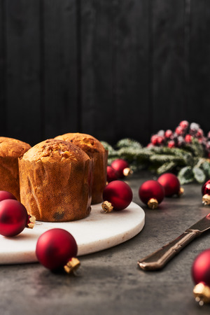 Traditional Christmas mini Panettone with raisins and dried fruits on white marble serving plate surrounded by red Christmas baubles on concrete table over black wooden background with copy space.