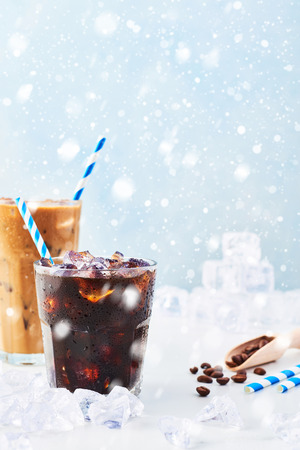 Winter drink iced coffee in a glass and ice coffee with cream in a tall glass, coffee beans and straws surrounded by ice on white marble table over blue background with snow. Copy space. Reklamní fotografie