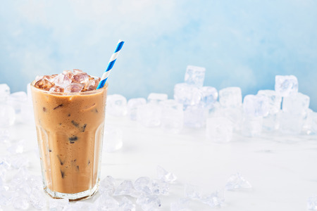 Summer drink ice coffee with cream in a tall glass with straw surrounded by ice on white marble table over blue background. Selective focus, copy space for text. Horizontal.
