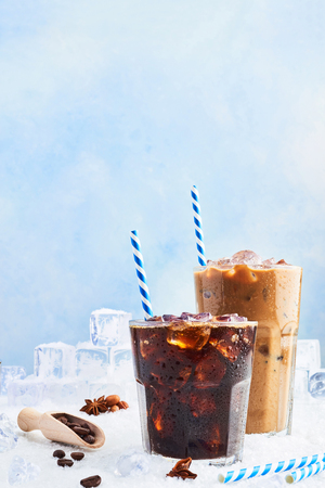 Summer drink iced coffee or soda in a glass and ice coffee with cream in a tall glass surrounded by ice cubes, coffee beans and various spices on snow over blue background. Copy space for text.