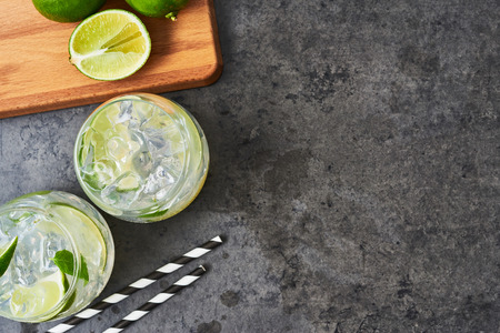 Lemonade or mojito with lime, mint and ice on dark concrete background. Copy space for text. Top view. Summer drink.