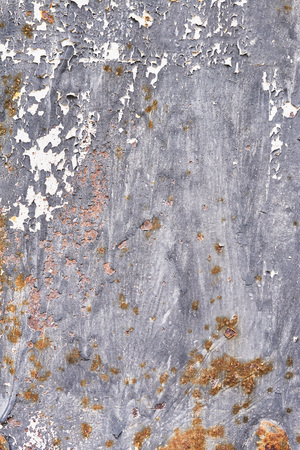 Rusty metal surface with dark blue paint flaking and cracking texture. Rusty metal background.
