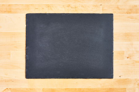 Black slate or black stone serving plate over wooden background. Copy space for text or design.