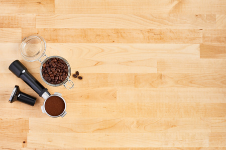 Portafilter with ground coffee, freshly roasted coffee beans in a glass jar and tamper on wooden background. Top view of coffee background. Flat lay. Copy space for text. Barista concept.
