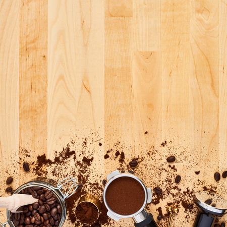 Assorted coffee beans, ground coffee, portafilter and tamper on wooden background. Top view of coffee background. Flat lay. Copy space for text. Barista concept. Square crop.