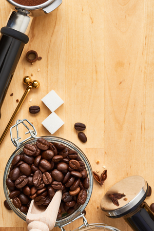 Freshly roasted coffee beans in a glass jar, portafilter and tamper on wooden background. Top view of coffee background. Flat lay. Copy space for text. Barista concept.