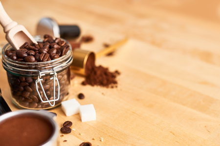 Freshly roasted coffee beans in a glass jar, portafilter, ground coffee and tamper on wooden background. Coffee background. Copy space for text. Barista concept.