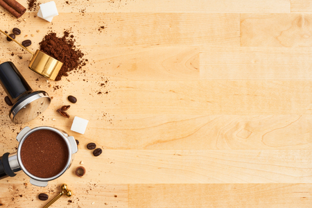 Assorted coffee beans, ground coffee, portafilter and tamper on wooden background. Top view of coffee background. Flat lay. Copy space for text. Barista concept.