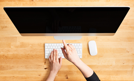 Female hands pointing at desktop computer. Top view of wooden office desk with large desktop computer, female hands on the keyboard and mouse. All in one computer. Simple modern workspace.