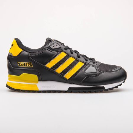 VIENNA, AUSTRIA - AUGUST 23, 2017: Adidas ZX 750 black and yellow sneaker on white background. Editorial