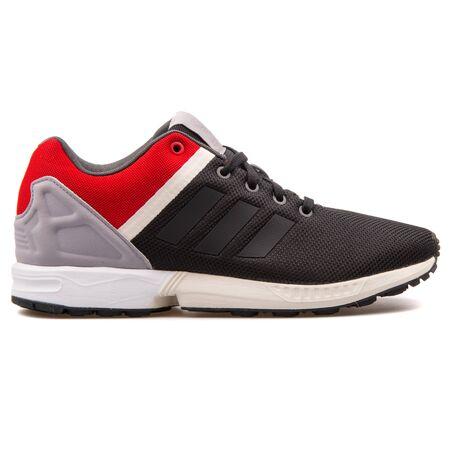 VIENNA, AUSTRIA - AUGUST 25, 2017: Adidas ZX Flux Split black, red, grey and white sneaker on white background.