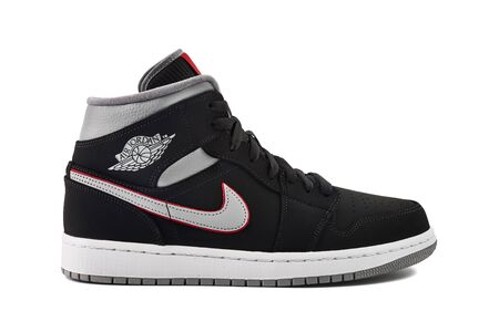 VIENNA, AUSTRIA - MAY 10, 2019: Nike Air Jordan 1 Mid black, grey, red and white sneaker on white background.