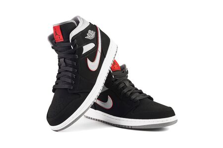 VIENNA, AUSTRIA - MAY 10, 2019: Nike Air Jordan 1 Mid black, grey, red and white sneakers on white background. 新闻类图片