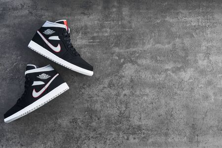 VIENNA, AUSTRIA - MAY 10, 2019: Nike Air Jordan 1 Mid black, grey, red and white sneakers on dark concrete background. Top view.