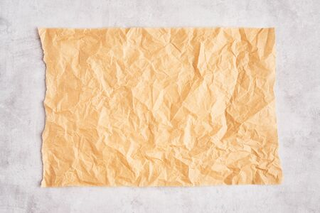 Crumpled piece of brown parchment or baking paper on grey concrete background. Top view. Copy space for text and design element.