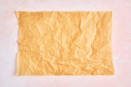 Crumpled piece of brown parchment or baking paper on rose and white texture pattern background. Top view. Copy space for text and design element.