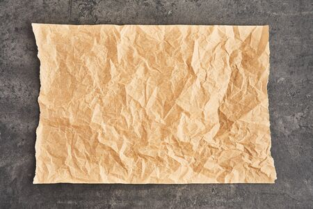 Crumpled piece of brown parchment or baking paper on black concrete background. Top view. Copy space for text and design element.