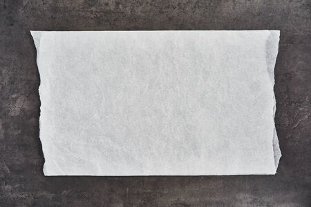 Crumpled piece of white parchment or baking paper on black concrete background. Top view. Copy space for text and design element.