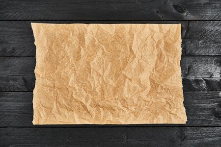 Crumpled piece of parchment or baking paper on black wooden table. Top view. Copy space for text and design element.