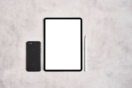 ZAGREB, CROATIA - SEPTEMBER 10, 2019: Top view of Apple iPad Pro, pencil and iPhone on grey concrete background. 新闻类图片