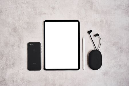 ZAGREB, CROATIA - SEPTEMBER 10, 2019: Top view of Apple iPad Pro, iPhone, pencil and Beats earphones on grey concrete background. 新闻类图片