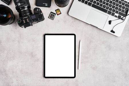 ZAGREB, CROATIA - SEPTEMBER 10, 2019: Top view on workplace of photographer or graphic designer. Apple iPad Pro, iPhone, MacBook Pro, Nikon Z6 mirrorless camera and lenses on grey concrete background.