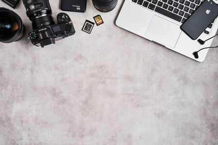 ZAGREB, CROATIA - SEPTEMBER 10, 2019: Top view on workplace of photographer. Apple MacBook Pro, iPhone, Nikon Z6 mirrorless camera, lenses and Beats earphones on grey concrete background. 新闻类图片