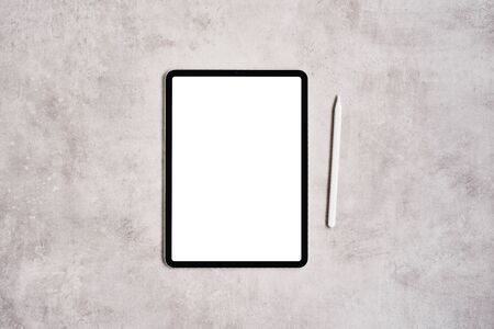 Black digital tablet with blank screen and pencil on grey concrete table. Flat lay. Copy space for text.