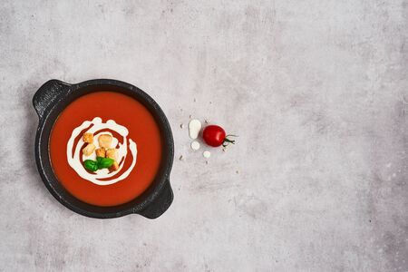 Tomato soup with cream, croutons and basil in a black bowl on stone background. Top view. Copy space for text.