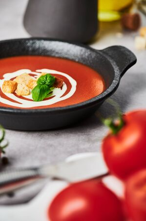 Delicious tomato soup with cream, croutons and basil in a black bowl on stone background. Copy space for text. Selective focus.
