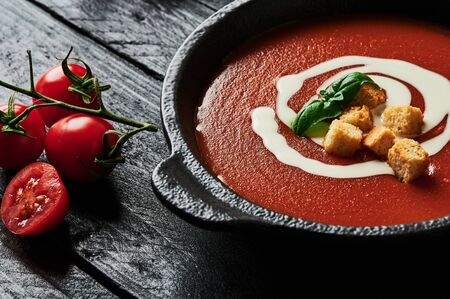 Tomato soup with cream, croutons and basil in a black bowl and tomatoes on black wooden background. Copy space for text. Selective focus. 免版税图像
