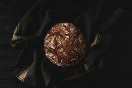 Freshly baked bread on black wooden background. Top view. Copy space.