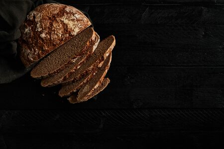 Sliced bread on black wooden background. Delicious freshly baked bread. Top view. Copy space. 免版税图像