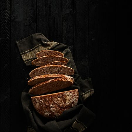 Sliced bread on black wooden background. Top view. Copy space. Square crop. 免版税图像