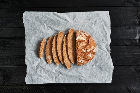Sliced bread on baking paper over black wooden background. Delicious freshly baked bread. Top view. Copy space.