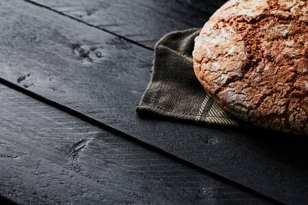 Freshly baked bread on black wooden background. Copy space. Selective focus.
