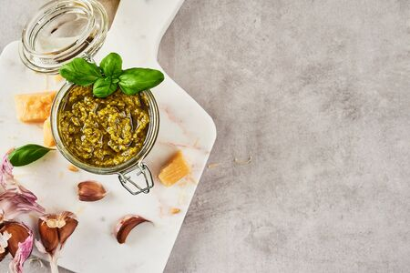Pesto sauce or pesto genovese in a glass jar with pine nuts, parmesan, basil, oil and garlic on white marble cutting board over grey stone background. Top view. Copy space.