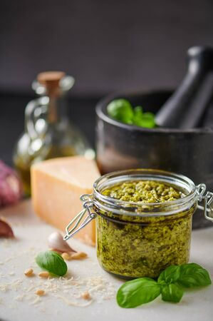 Pesto sauce or pesto genovese in a glass jar with pine nuts, parmesan, basil, oil and garlic on white marble cutting board. Copy space.